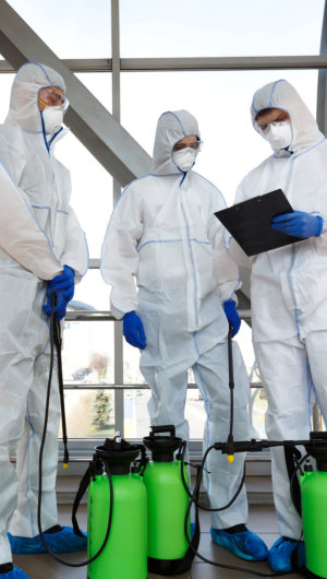 People in virus protective suits reading plan of city disinfection with spray, copy space, coronavirus epidemic